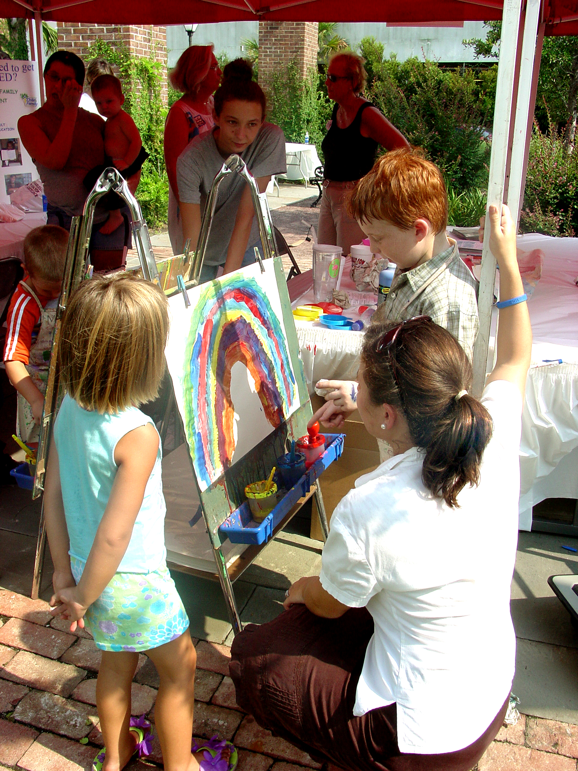 Woman helps children paint a picture of a rainbow at outdoor event
