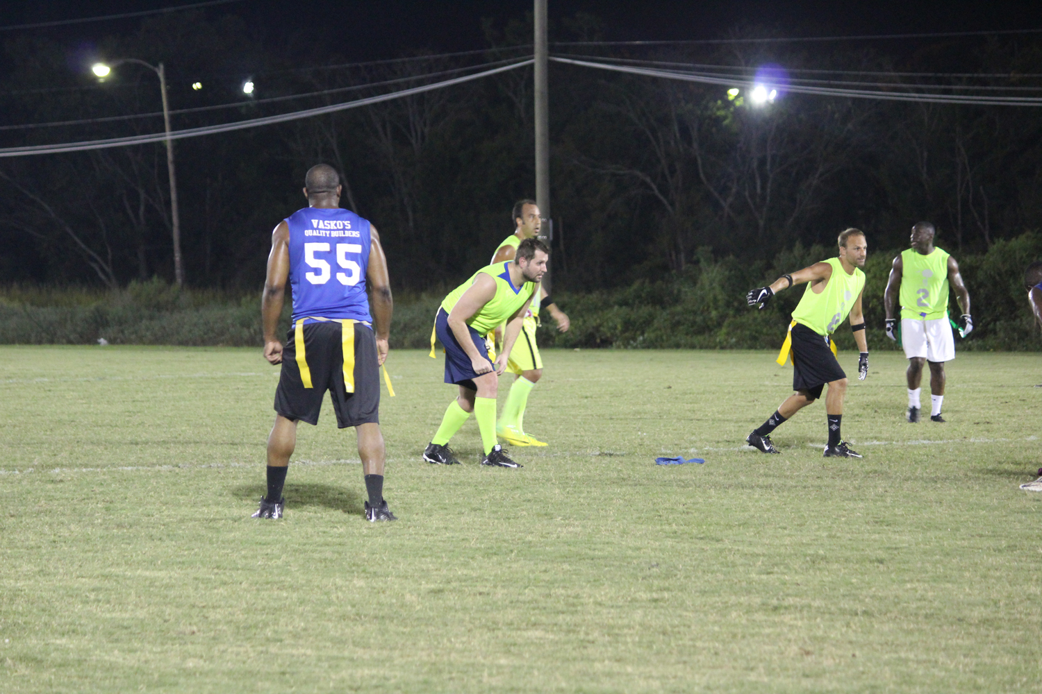 men playing flag football at night