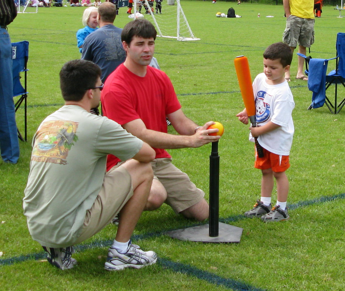 Two adults helping child at t ball
