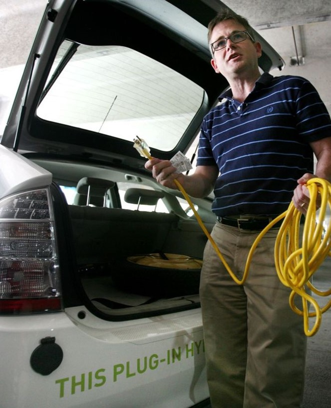 Man plugging in his electric vehicle