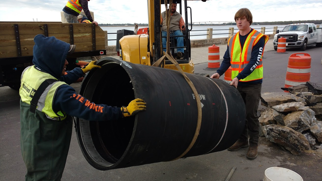Men preparing large pipe to be laid into the ground